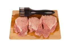 Battez la viande sur un conseil en bois sur un fond blanc Photo stock