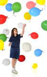 Batting Balloons. An elementary girl batting a barage of falling balloons Stock Photo
