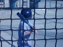 Batting Cage. Boy learning how to hit ball in batting cage Royalty Free Stock Images