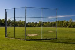 Batting Cage. A view from behind a baseball batting cage at a local park Royalty Free Stock Images