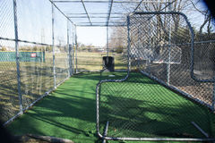 Batting cage with the pitchers screen. A local high schools batting cage from behind the pitchers safety screen Stock Photo
