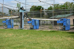 Batting cages. Pitching machines behind a fence at batting cages Royalty Free Stock Photography