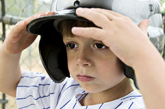 Batting Helmet. Little boy holding his batting helmet on his head Royalty Free Stock Images