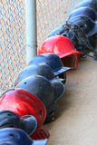 Batting helmets. A row of batting helmets in the dugout Stock Photos