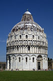 Battistero di San Giovanni-The Baptistery in Pisa,Italy. Vertical photo of the Baptistery in Pisa with blue sky and green grass Stock Photos