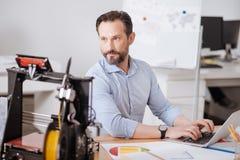 Battitura a macchina barbuta piacevole dell'uomo Immagini Stock Libere da Diritti