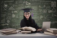 Battitura a macchina laureata della femmina asiatica sul computer portatile nella classe Immagine Stock