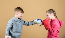 Battle for attention. Child sporty athlete practicing boxing skills. Boxing sport. Children wear boxing gloves while. Fighting beige background. Attack and stock images