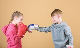 Battle for attention. Child sporty athlete practicing boxing skills. Boxing sport. Children wear boxing gloves while. Fighting beige background. Attack and stock photo