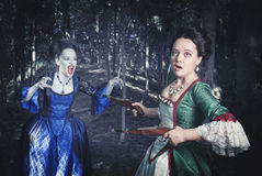 Battle with beautiful vampire in medieval dress Royalty Free Stock Images