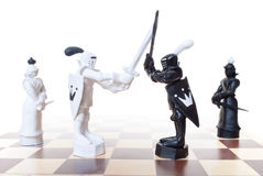 Battle chess. Chess pieces on a chess board Royalty Free Stock Images