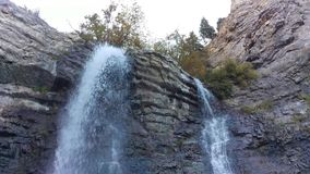 Battle Creek Falls Loop in Autumn. A loop of Battle Creek Falls cascading down the layered rock canyon wall stock footage