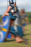 Battle Fatigue. Roman Soldier pauses in battle and one falls to knees in exhaustion Stock Photo