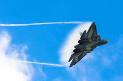 Battle fighter jet flying dives breaking clouds on a blue sky disruption of air flow.  Stock Images
