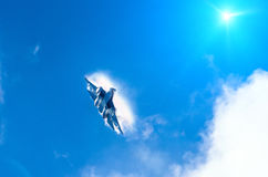 Battle fighter jet flying dives breaking clouds on a blue sky sun light.  Stock Images