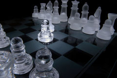 Battle of the pawns. A glass chess set on black background stock photos