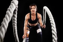Battle ropes session. Attractive young fit and toned sportswoman working out in functional training gym doing crossfit. Portrait of a fit and muscular woman Royalty Free Stock Photo