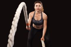 Battle ropes session. Attractive young fit and toned sportswoman working out in functional training gym doing crossfit Stock Photography