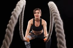 Battle ropes session. Attractive young fit and toned sportswoman working out in functional training gym doing exercise royalty free stock photos