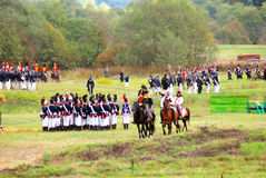 A battle scene. MOSCOW REGION - SEPTEMBER 07, 2014: A battle scene. Many soldiers-reenactors standing, marching and riding horses. Borodino historical Stock Photos