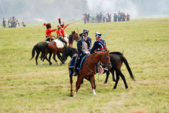 A battle scene. MOSCOW REGION - SEPTEMBER 07, 2014: A battle scene.  Reenactors dressed as Napoleonic war soldiers ride horses at Borodino battle historical Stock Photo