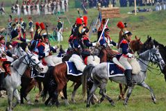 A battle scene. MOSCOW REGION - SEPTEMBER 07, 2014: Reenactors dressed as Napoleonic war soldiers ride horses at Borodino battle historical reenactment Royalty Free Stock Photo