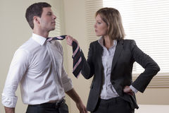 Battle of the sexes. Business woman pullling his colleague from necktie Royalty Free Stock Photo