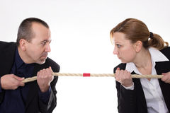 Battle of the sexes. Man and women pulling a rope against each other Royalty Free Stock Photos