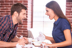 Battle of the sexes. Side view image of angry men and women sitting face to face at the office table and shouting at each other Royalty Free Stock Photos