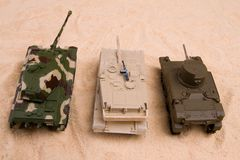 Battle of the tank toys. Battle tank toys on the dessert royalty free stock photography
