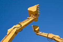 Battle of titans. Two back hoe diggers high in sky Stock Photo