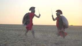The battle of two Roman soldiers in red cloaks in the middle of the field before dawn. Roman warriors in armor of leather and red cloaks fight with swords and stock footage