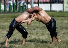 A battle between two wrestlers at the Kirkpinar Turkish Oil Wrestling Festival at Edirne in Turkey. Stock Photo