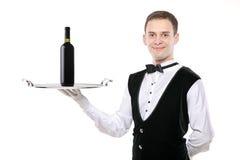 Battler, der ein silbernes Tellersegment mit Weinflasche anhält Stockbilder