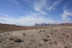 Battleship Butte, Utah, USA. Battleship Butte near Green River, Utah, set against a blue sky with wispy cirrus clouds. Cacti litter the barren semi desert Stock Image