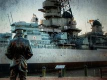 Battleship. The Lone Sailor standing in from of the battleship USS Wisconsin in a textured image stock photos