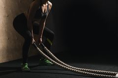 Battling ropes girl at gym workout exercise fitted body. Athletic young woman doing some crossfit exercises with a rope outdoor Royalty Free Stock Photos