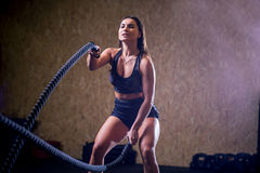 Battling ropes girl at gym workout exercise fitted body Royalty Free Stock Photos