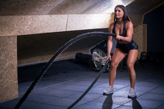 Battling ropes girl at gym workout exercise fitted body Stock Photography