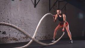 Battling ropes girl at gym workout exercise fitted body. Slow motion. Battling ropes girl at gym workout exercise fitted body stock video footage