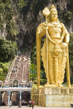Batu Cave and Statue. A beautiful statue standing tall by stairs leading to a cave Royalty Free Stock Images