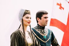 Batumi, Adjara, Georgia - May 26, 2016: Young couple of man and. Woman in Georgian national clothes on flag background in celebration of the national holiday Stock Photo