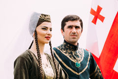 Batumi, Adjara, Georgia - May 26, 2016: Young couple of man and woman in Georgian national clothes on flag background Royalty Free Stock Image