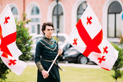 Batumi, Adjara, Georgia - May 26, 2016: Young man in Georgian na. Tional dress holding a national flag in celebration of the national holiday - the Independence Royalty Free Stock Image