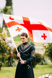 Batumi, Adjara, Georgia - May 26, 2016: Young man in Georgian na. Tional dress holding a national flag in celebration of the national holiday - the Independence Royalty Free Stock Photos