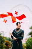 Batumi, Adjara, Georgia - May 26, 2016: Young man in Georgian na. Tional dress holding a national flag in celebration of the national holiday - the Independence Stock Photo