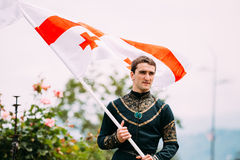Batumi, Adjara, Georgia - May 26, 2016: Young man in Georgian national dress holding. A national flag in celebration of the national holiday - the Independence Stock Photos