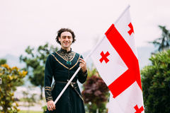 Batumi, Adjara, Georgia - May 26, 2016: Young man in Georgian national dress holding. A national flag in celebration of the national holiday - the Independence Royalty Free Stock Photos