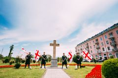 Batumi, Adjara, Georgia - May 26, 2016: Young men in Georgian national dress holding a national flags in celebration of Royalty Free Stock Photo
