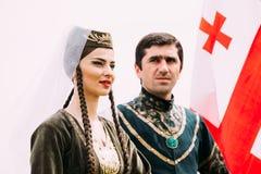 Batumi, Adjara Gruzja, Maj, - 26, 2016: Młoda para mężczyzna i kobieta w Gruzińskim obywatelu odziewa na chorągwianym tle Obraz Royalty Free
